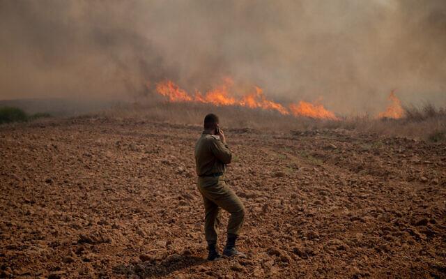 Un soldat se tient devant un incendie à proximité du kibboutz Beeri dans le sud d'Israël. L'incendie a été déclenché par un engin incendiaire accroché à un ballon depuis la bande de Gaza, le 13 août 2020. (Yonatan Sindel/Flash90)