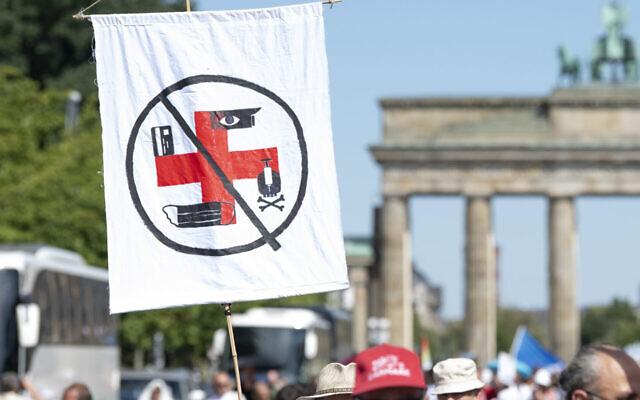 Le 1 août 2020 à Berlin, un drapeau sur lequel on peut voir différent symboles accrochés à une croix rouge former une croix gammée est tenu par un participant dans la manifestation contre les restrictions liées au coronavirus devant la Porte de Brandenburg. (Fabian Sommer/picture alliance via Getty Images via JTA)