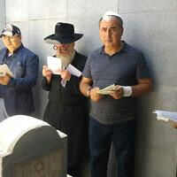 Des hommes prient autour de la tombe de  Levi Yitzchak Schneerson à Almaty, au Kazakhstan, en 2016. (Autorisation du mouvement 'Habad Kazakhstan via JTA)