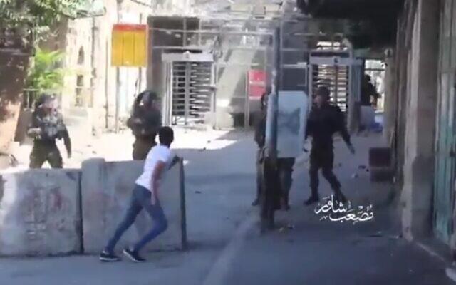 Un extrait de vidéo montre un jeune Palestinien lançant des pierres à bout portant sur des soldats de Tsahal à Hébron, le 29 août 2020. (Capture d'écran vidéo)