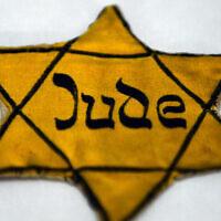 """L'étoile jaune, que les Juifs étaient forcés de porter pendant le règne nazi, où l'on peut lire """"Juif"""", est exposée dans une vitrine du mémorial de Wewelsburg à Bueren-Wewelsburg, en Allemagne, le 22 janvier 2015. (Photo par Caroline Seidel/picture alliance via Getty Images)"""
