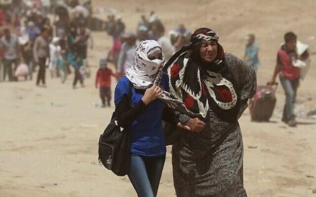 Photo d'illustration : Des réfugiés syriens traversent la frontière avec l'Irak au poste-frontière de Peshkhabour, à Dahuk, à 430 kilomètres au nord-ouest de Bagdad, en Irak. Les scientifiques avertissent que le changement climatique va compliquer et empirer les menaces sécuritaires dans le monde comme les guerres civiles, les conflits entre nations et le problème des réfugiés. Photo prise le 20 août 2013 (Crédit :  AP Photo/Hadi Mizban, File)