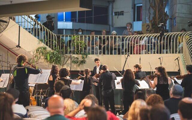 Ido Shpitalnik, chef d'orchestre du Jerusalem Street Orchestra, lors du seul concert qu'il a été aurotisé à organiser depuis le début de l'épidémie de coronavirus. (Autorisation : Jerusalem Street Orchestra)