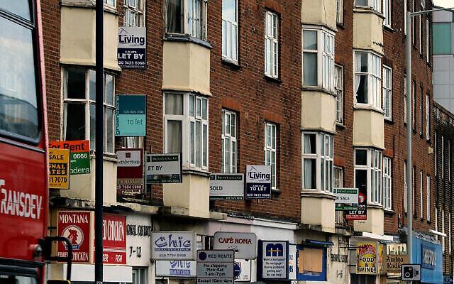 Un agent immobilier signe devant des maisons proposées à la vente et à la location, à Londres, le 8 octobre 2013. (AP Photo/Lefteris Pitarakis)