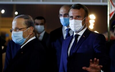 Le président français Emmanuel Macron (à droite) et le président libanais Michel Aoun, tous deux portant des masques en raison de la pandémie de Covid-19, à l'aéroport international de Beyrouth, le 31 août 2020. (GONZALO FUENTES / POOL / AFP)