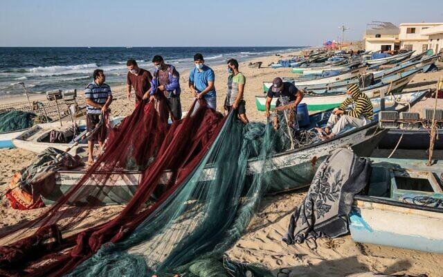 Des pêcheurs palestiniens, masqués en raison de la pandémie de coronavirus COVID-19, préparent leurs filets de pêche sur une plage de la Méditerranée à Rafah, dans le sud de la bande de Gaza, le 2 septembre 2020. (SAID KHATIB / AFP)