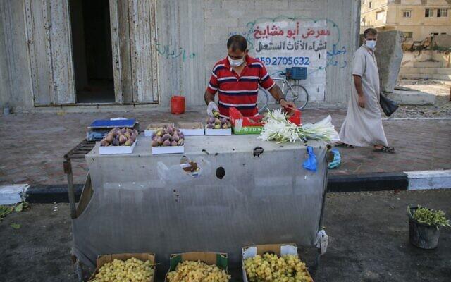 Un vendeur palestinien masqué dispose des produits dans une rue de la ville de Gaza, le 3 septembre 2020, alors qu'une pandémie de coronavirus COVID-19 impose un confinement. (MOHAMMED ABED / AFP)