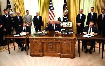 Le président américain Donald Trump observe le Premier ministre kosovar Avdullah Hoti (à droite) et le président serbe Aleksandar Vucic (à gauche) signer un accord sur l'ouverture de relations économiques, dans le bureau ovale de la Maison Blanche à Washington, DC, le 4 septembre 2020. (Photo de Brendan Smialowski / AFP)