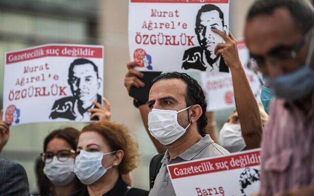 Des manifestants réunis devant un tribunal d'Istanbul brandissent des portraits des journalistes emprisonnés sur le point d'être jugés, le 9 septembre 2020, (Crédit : Ozan KOSE / AFP)