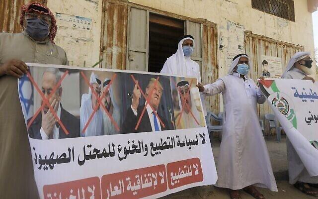 Des Palestiniens brandissent une pancarte comportant les portraits barrés de Benjamin Netanyahu, du prince héritier d'Abou Dhabi Mohammed bin Zayed Al Nahyane, du gouverneur de Dubaï Mohammed bin Rashid Al Maktoum, du président américain Donald Trump et du roi du Bahreïn Hamad bin Isa Al Khalifa, lors d'une manifestation organisée par le Hamas dans la bande de Gaza, à Deir al-Balah, le 12 septembre 2020, pour condamner l'accord de normalisation Israël-Bahreïn. (Mahmud Hams/AFP)
