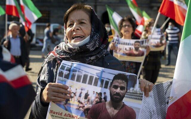 Une femme tient un portrait du lutteur iranien Navid Afkari lors d'une manifestation sur la place du Dam à Amsterdam, aux Pays-Bas, le 13 septembre 2020, contre son exécution dans la ville de Shiraz, dans le sud de l'Iran, et contre le gouvernement iranien. (Evert Elzinga / ANP / AFP)