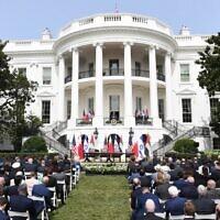 Le public regarde le président américain Donald Trump s'exprimer depuis le balcon Truman de la Maison Blanche lors de la cérémonie de signature des Accords d'Abraham par lesquels les pays du Bahreïn et des Emirats Arabes Unis normalisent leurs relations avec Israël, sur la pelouse sud de la Maison Blanche à Washington, DC, le 15 septembre 2020. (SAUL LOEB / AFP)