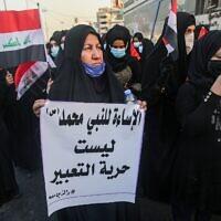 """Une femme portant un masque contre le coronavirus brandit une affiche disant en arabe : """"insulter le prophète Mahomet n'est pas de la liberté d'expression"""" lors d'une manifestation devant l'ambassade de France en Irak, à Bagdad, le 17 septembre 2020. (Crédit : AHMAD AL-RUBAYE / AFP)"""