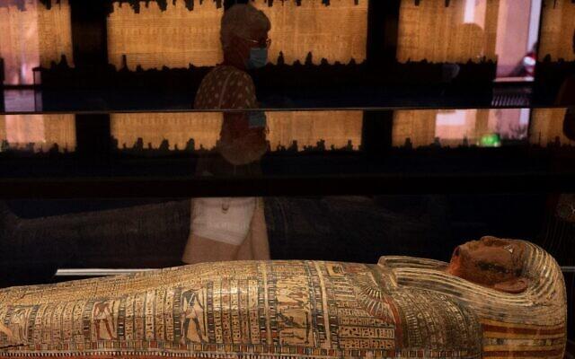 """Des visiteurs marchent le long d'un sarcophage durant l'exposition """"Pharaon, Osiris et momie"""" au musée Granet à Aix-en-Provence, dans le sud-est de la France, le 18 septembre 2020. L'exposition aura lieu du 19 septembre au 14 février 2021. (Christophe SIMON / AFP)"""