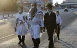 Des Juifs ultra-orthodoxes portant le masque vont à la synagogue en empruntant une rue vide pour les prières de Rosh Hashana à Jérusalem dans le cadre du nouveau confinement national, le 19 septembre 2020 (Crédit : Menahem Kahana/AFP)