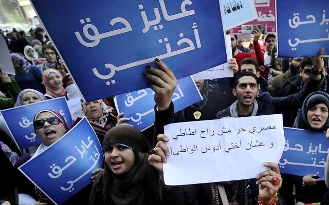 Dans cette photo d'archive prise le 27 décembre 2011, des femmes égyptiennes tiennent des pancartes sur lesquelles on peut lire en arabe «Je veux les droits pour ma sœur» alors qu'elles protestent contre les violations du conseil militaire et les tests de virginité sur les femmes, devant le tribunal du Conseil d'État au Caire. (Filippo MONTEFORTE / AFP)