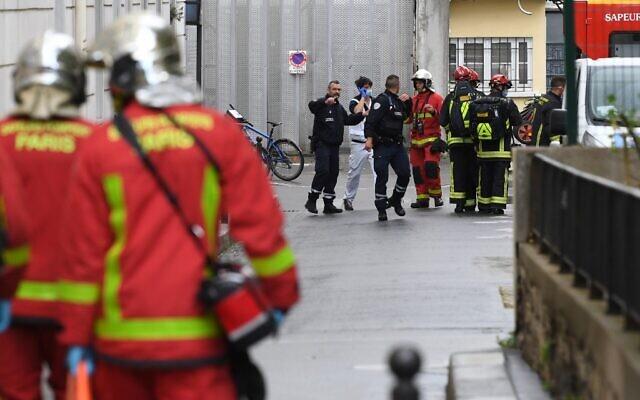 """Des pompiers transportent un blessé dans une ambulance près des anciens bureaux du journal satirique français """"Charlie Hebdo"""" suite à une agression à l'arme blanche, à Paris, le 25 septembre 2020. (Alain Jocard / AFP)"""