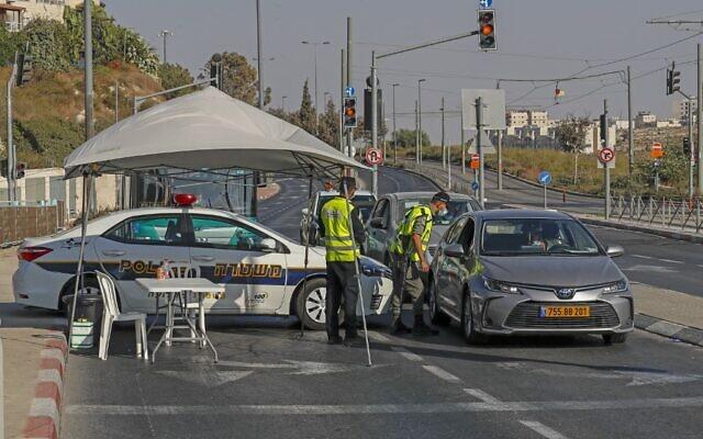 Des policiers israéliens arrêtent une voiture à un checkpoint à Jérusalem-Est pour faire appliquer le confinement national mis en place dans la lutte contre le coronavirus, le 25 septembre 2020 (Crédit :  AHMAD GHARABLI / AFP)