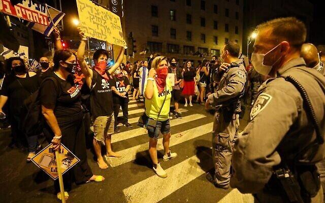 Des manifestants israéliens au cours d'une manifestation, en plein confinement, devant la résidence du Premier ministre Benjamin Netanyahu à Jérusalem, réclamant sa démission, le 26 septembre 2020 (Crédit : EMMANUEL DUNAND / AFP)