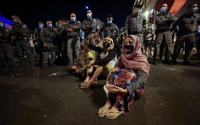 Des manifestants assis près des policiers au cours d'une manifestation devant la résidence du Premier ministre Benjamin Netanyahu à Jérusalem, le 26 septembre 2020 (Crédit :  Emmanuel DUNAND / AFP)