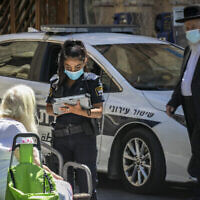 Une policière donne une amende à une femme pour non-port du masque à Jérusalem, le 24 juin 2020 (Crédit : Olivier Fitoussi/Flash90)