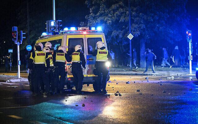 Des manifestants lancent des pierres sur la police lors d'échauffourées dans le quartier de Rosengard à Malmö, en Suède, 28 août 2020. (Crédit : TT News Agency via AP)