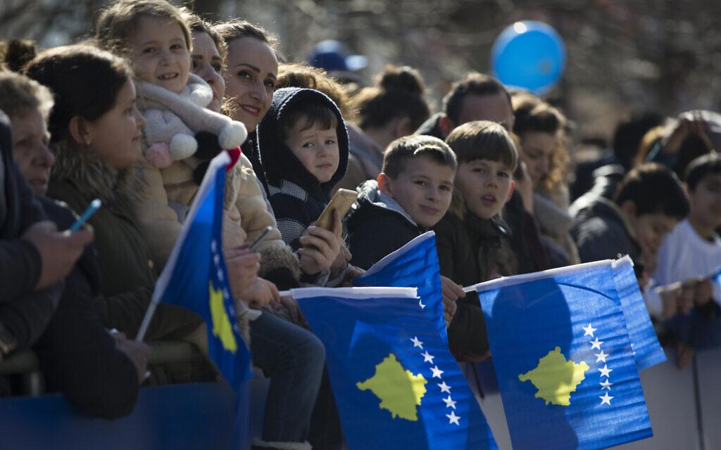 Des Kosovars agitent des drapeaux nationaux en attendant de voir un défilé militaire, lors des célébrations du 11e anniversaire de l'indépendance à Pristina, le 17 février 2019. (AP Photo/Visar Kryeziu)