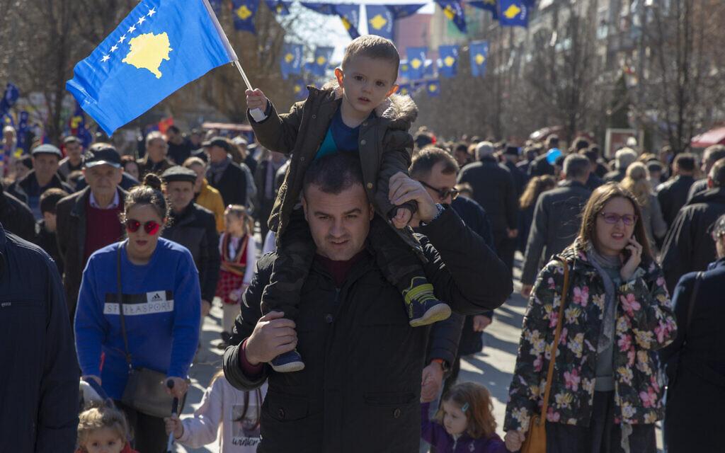 Un père tient son fils sur ses épaules qui brandit le drapeau du Kosovo alors qu'ils célèbrent le 12e anniversaire de l'indépendance du pays, dans la capitale Pristina, le lundi 17 février 2020 (AP Photo/Visar Kryeziu)