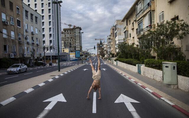 Un Israélien se tient sur les mains sur une route déserte pendant le bouclage qui fait suite aux mesures gouvernementales visant à stopper la propagation du coronavirus, à Tel Aviv, le 8 avril 2020. (AP Photo/Oded Balilty)