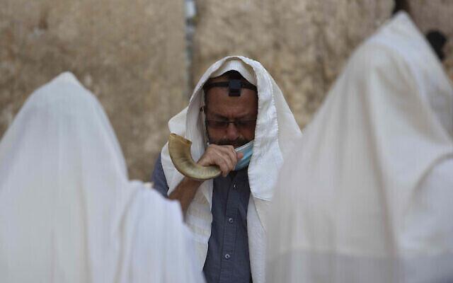 Un Juif souffle dans le Shofar lors d'une prière au mur Occidental, dans la Vieille Ville de Jérusalem, le 16 septembre 2020 (Crédit : AP Photo/Sebastian Scheiner)