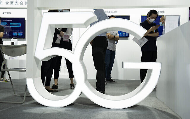 Des visiteurs portant des masques contre le coronavirus passent devant un sigle 5G géant à la China Beijing International High Tech Expo, à Pékin, le 17 septembre 2020. (Crédit : AP Photo/Ng Han Guan)