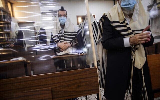 Des Juifs ultra-orthodoxes portent le masque pendant la prière du matin dans une synagogue agrémentée de séparations en plastique, à Bnei Brak, en Israël, le 18 septembre 2020 (Crédit : AP Photo/Oded Balilty)
