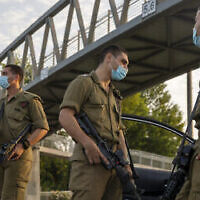 Des soldats israéliens portent des masques faciaux à un barrage routier de la police à Tel Aviv pendant le confinement national en raison de la pandémie de coronavirus, le 19 septembre 2020. (AP Photo / Ariel Schalit)