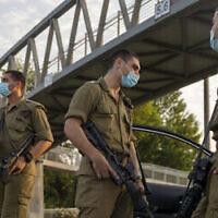 Des soldats israéliens portent des masques faciaux à un barrage routier de la police à Tel Aviv pendant le confinement national en raison de la pandémie de coronavirus, le 19 septembre 2020. (AP Photo / Ariel Schalit)