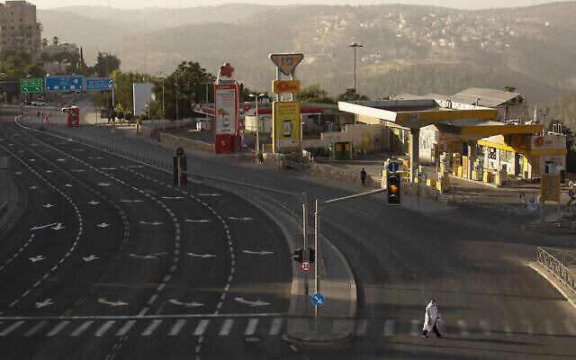 Un homme, arborant un châle de prière, traverse une artère principale de Jérusalem à Yom Kippour, le jour du pardon et la fête la plus sainte du calendrier juif, en plein confinement national, le 28 septembre 2020 (Crédit : AP Photo/Maya Alleruzzo)