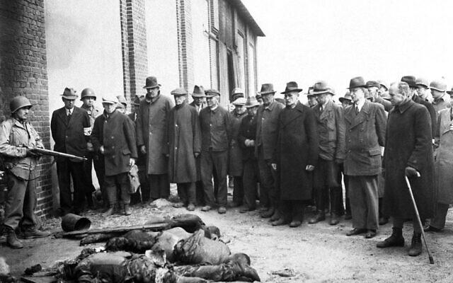Les Bürgermeister des villes voisines qui entouraient le campsde concentration  de Gardelegen, en Allemagne, constatent les atrocités commises dans une cour de ferme aux abords de la ville, une photo prise par des soldats de la. Ninth Army  américaine, le 18 avril 1945 (Crédit : AP Photo)