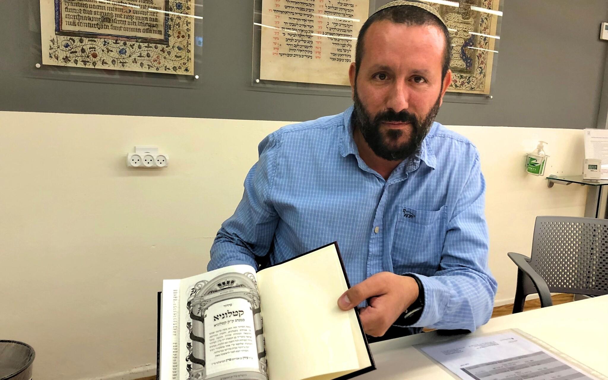 """Le Dr Idan Perez tient le """"Siddour Catalunya"""", une reconstitution du livre de prières utilisé dans certaines parties de la Catalogne avant l'expulsion, à la Bibliothèque nationale de Jérusalem, le 15 septembre 2019. (Amanda Borschel-Dan/Times d'Israël)"""