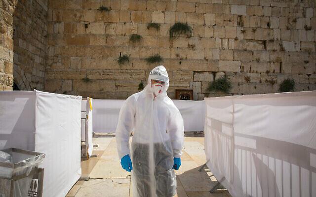 Un étudiant orthodoxe de séminaire talmudique vêtu d'une tenue de protection, de gants et d'un masque prie au mur Occidental à Jérusalem, le 3 septembre 2020. (Olivier Fitoussil/Flash90)