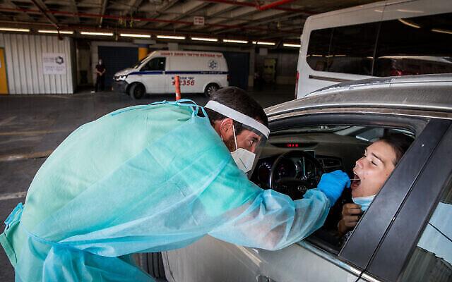 Un employé de l'hôpital Shaare Zedek, en habit de protection, prélève un échantillon sur une femme pour un test de dépistage au coronavirus (COVID-19) à Jérusalem, le 14 septembre 2020. (Crédit :  Nati Shohat/Flash90)