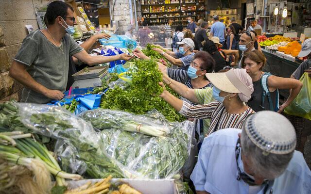 Des Israéliens, portant des masques faciaux par crainte du coronavirus, font leurs courses au marché Mahane Yehuda à Jérusalem, le 14 septembre 2020. (Olivier Fitoussi/Flash90)