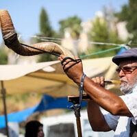 Un Israélien souffle dans le Shofar au marché de la ville de Safed, dans le nord du pays, le 16 septembre 2020 (Crédit : David Cohen/Flash90)