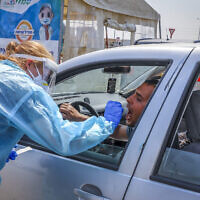 Une employée de la Clalit réalise un test de dépistage à la cOVID-19 dans un centre de type drive-in à Lod, le 17 septembre 2020 (Crédit : Yossi Aloni/FLASH90)