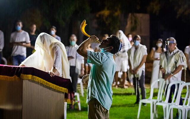 Un homme souffle dans le Shofar à la fin de Yom Kippour, la journée du pardon, dans un espace public du Moshav Haniel, le 28 septembre 2020 (Crédit :  Chen Leopold/Flash90)