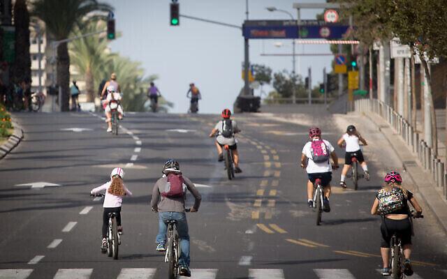 Des Israéliens font du vélo sur une route désertée de Tel Aviv à Yom Kippour, le 28 septembre 2020 (Crédit : Miriam Alster/Flash 90)
