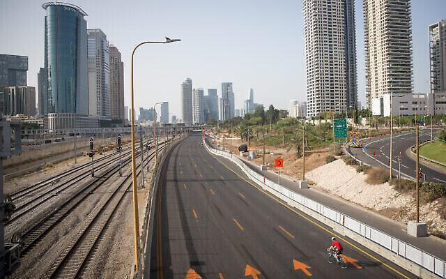 Des Israéliens font du vélo sur l'autoroute d'Ayalon déserté à Tel Aviv à Yom Kippour, le jour du pardon et la fête la plus sainte du calendrier juif, le 28 septembre 2020 (Crédit : Miriam Alster/Flash 90)