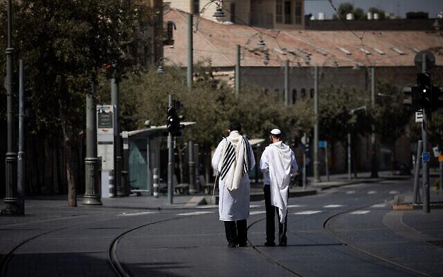 Des hommes Juifs marchent à Jérusalem, arborant leurs châles de prière, à Yom Kippour, le 28 septembre 2020 (Crédit :Yonatan Sindel/Flash90)