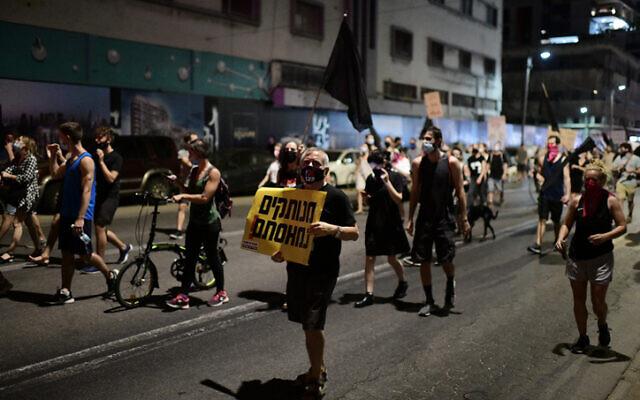 Des Israéliens manifestent contre le gouvernement aux abords du siège de la police israélienne dans le district de Tel Aviv, le 29 septembre 2020 (Crédit : Tomer Neuberg/Flash90)