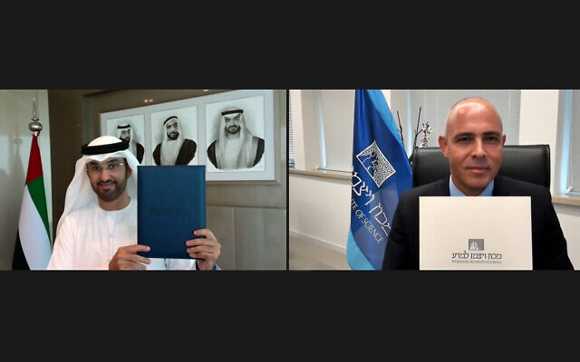 Alon Chen (à droite), directeur de l'Institut Weizmann des sciences, et le sultan Ahmed Al Jaber brandissent des copies du protocole d'accord signé entre l'institut basé à Rehovot et l'Université d'intelligence artificielle Mohamed bin Zayed. (Avec l'aimable autorisation de l'Institut Weizmann des sciences)