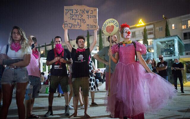 """Des manifestants anti-gouvernment à Tel Aviv avant le début du second confinement national, le 17 septembre 2020. La pancarte : """"Quand l'injustice devient loi, la rébellion devient une obligation"""". (Miriam Alster/Flash90)"""