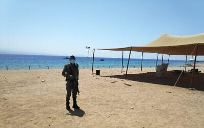 Un officier de police patrouille sur une plage d'Eilat après qu'un Jordanien a été suspecté d'être entré en Israël en nageant depuis la Jordanie, le 2 septembre 2020. (Crédit : police israélienne)